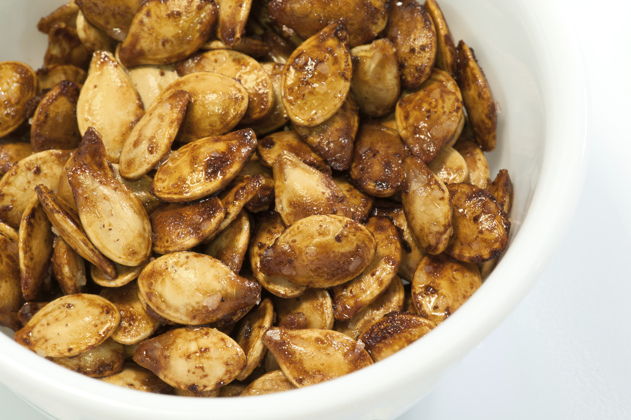 Close-up of Roasted Pumpkin Seeds in White Bowl, Neutral Background