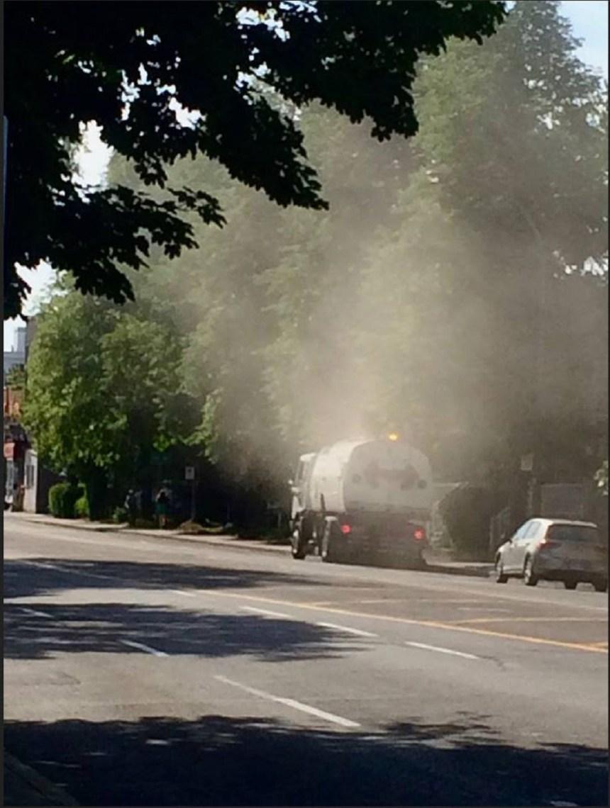 Un engin de l'arrondissement répand dans les airs la poussière qu'il balaie au sol