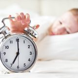the alarm clock and a sleeping young woman