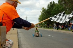 Co-founder of the Dorval Soapbox Derby, Jean-Guy Aubry, waves the checkered flag at the finish line on Fénelon Blvd. on Sunday, Sept. 11.