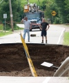 Hydro Quebec workers survey the scene where a section of road on a causeway collapsed following an earthquake in Bowman, Quebec Wednesday June 23, 2010. THE CANADIAN PRESS/Adrian Wyld