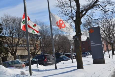 Les drapeaux sont en berne devant la mairie de Saint-Laurent en guise d'appui aux résidents de la capitale nationale. (Collaboration spéciale/Arrondissement de Saint-Laurent)