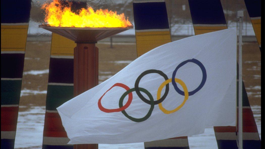 Le drapeau des Jeux olympiques devant la flamme olympique