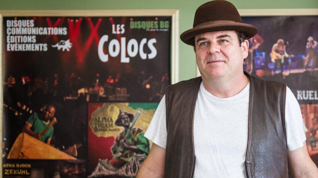 Benoit Gagné, musicien et producteur des Colocs, devant des affiches du groupe mythique.