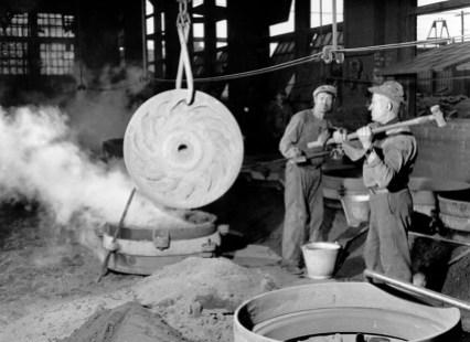 Une image d'époque des shops Angus. Deux travailleurs s'affairent sur une pièce de métal.