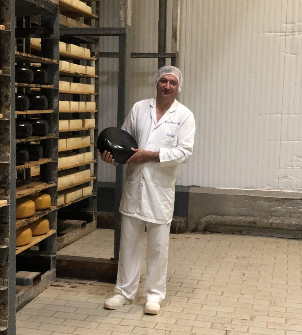 Fromager dans une usine tenant une meule de fromage à la peau noire