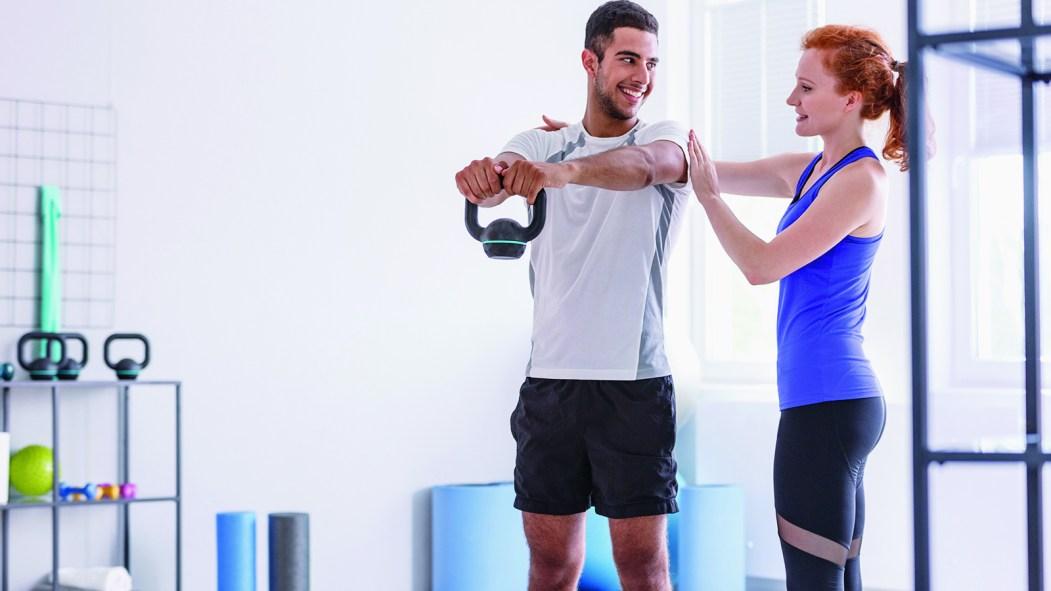 Une kinésiologue aide un athlète avec un mouvement de musculation.