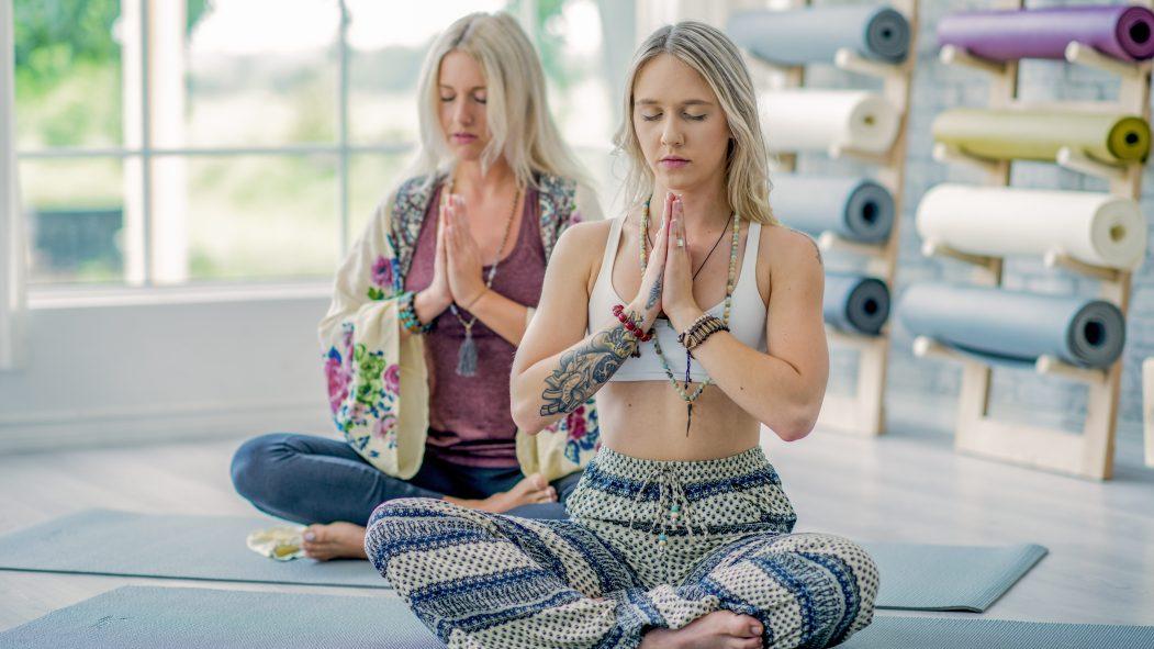 Deux femmes méditent lors d'une séance de yoga