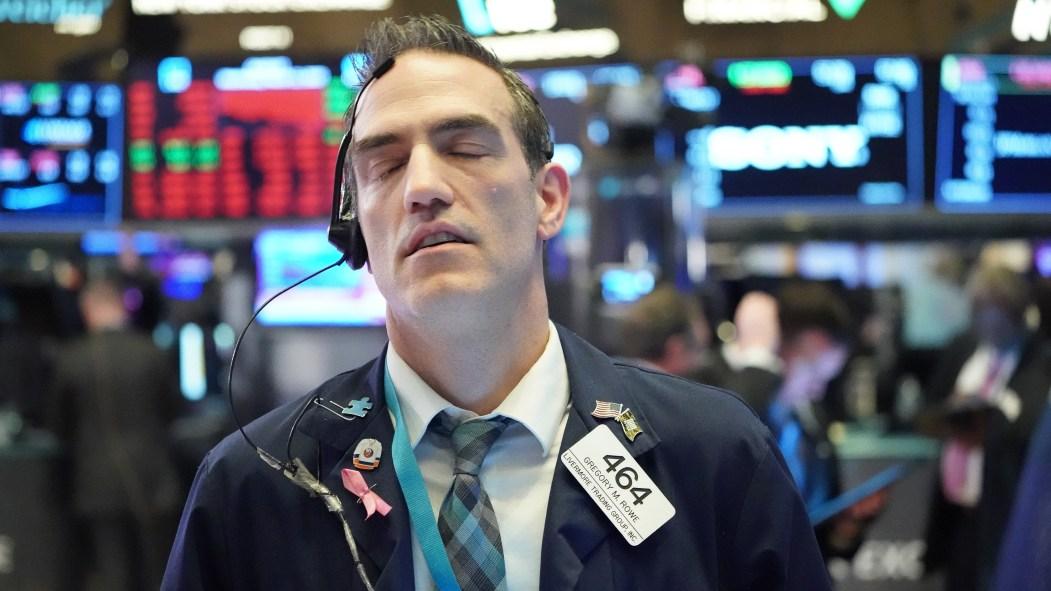 Un homme ferme les yeux devant la chute des indices boursiers à Wallstreet, après une panique due au coronavirus.