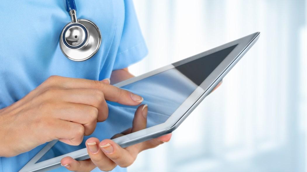 Un médecin consultant sa tablette pour trouver des bénévoles.