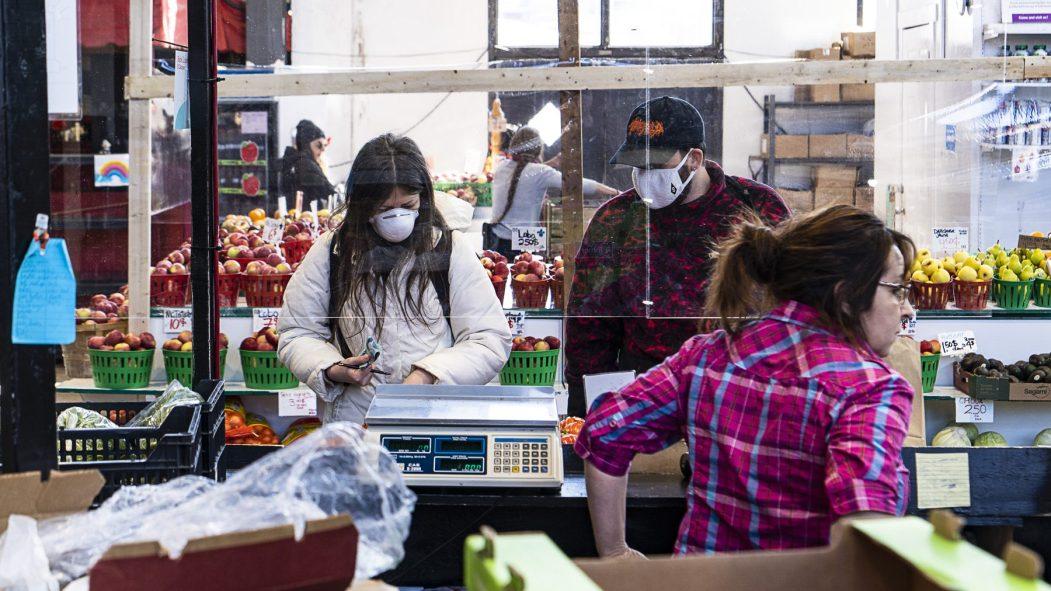 Les étals de fruits et légumes du Marché Jean-Talon protégés par des panneaux de plastique.