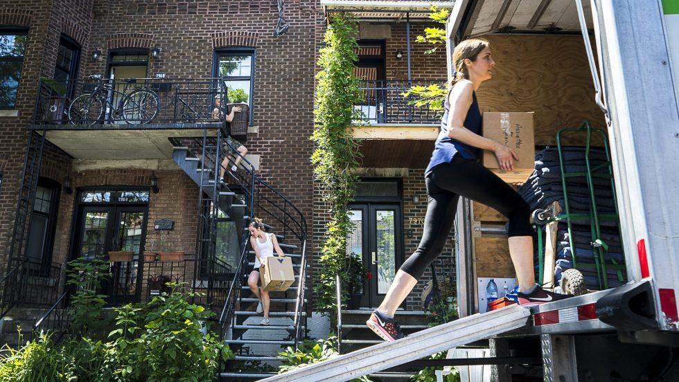 Une femme transporte une boîte dans un camion lors de la journée du déménagement du 1er juillet. En arrière plan, deux autres personnes descendent des escaliers avec des boîtes.