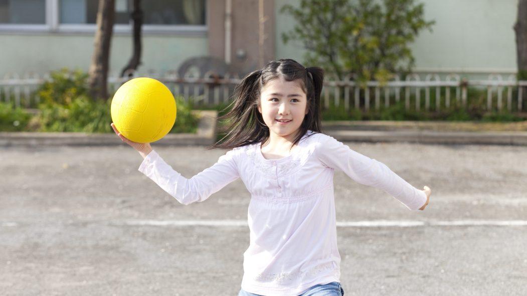 Une jeune fille joue au ballon-chasseur.