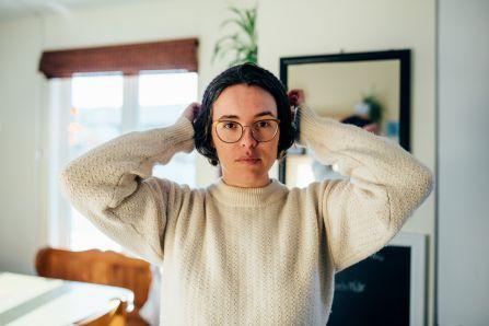 Une femme tient des écouteurs sur ses oreilles