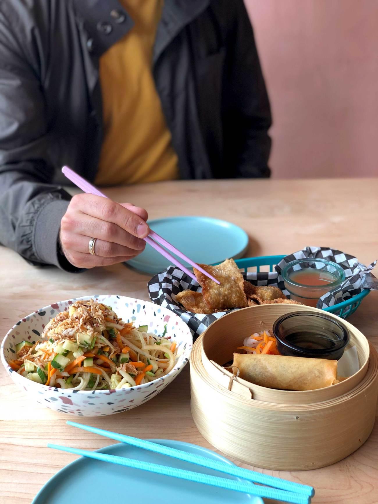 Plusieurs plats vietnamiens déposés sur une table avec la silhouette d'un homme qui prend un ravioli avec une baguette.