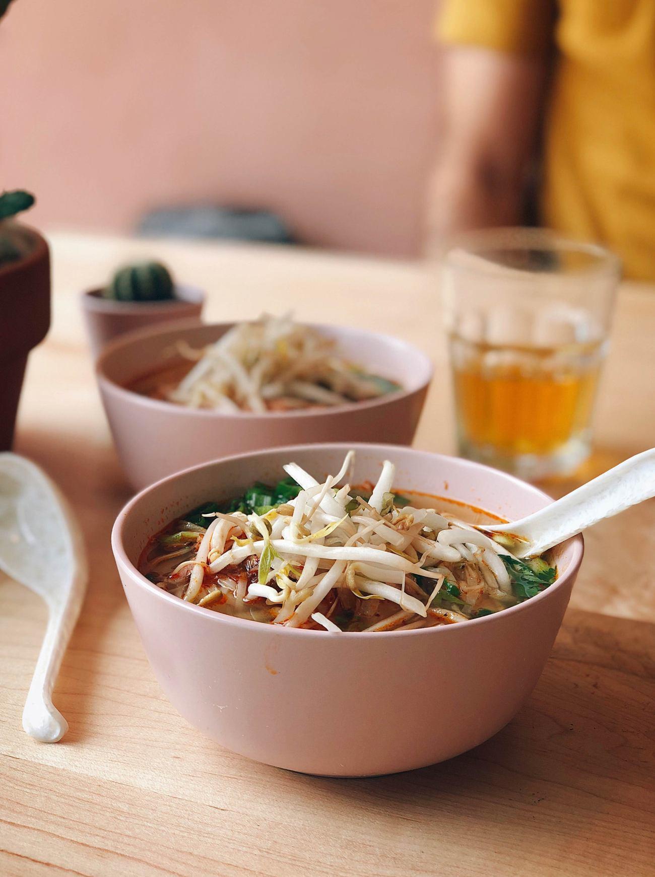 Soupe tonkinoise déposée sur une table avec d'autres plats en arrière plan