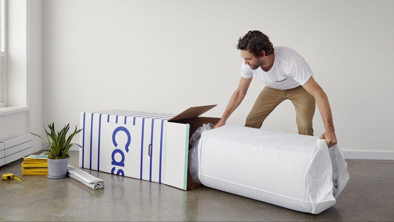 Homme sortant un matelas de sa boîte dans nouvel appartement