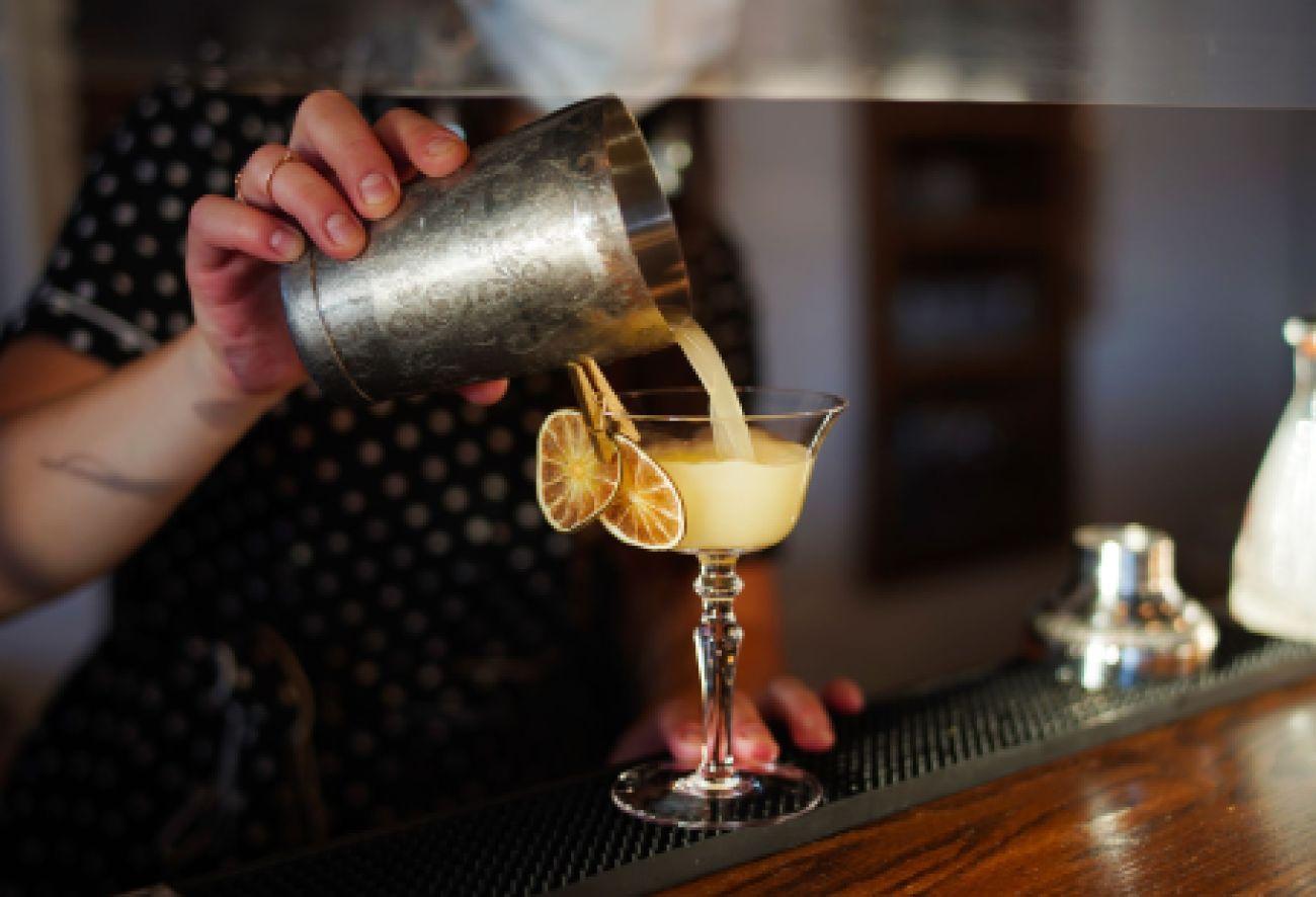 mixologue qui verse un cocktail dans un verre déposé sur un bar