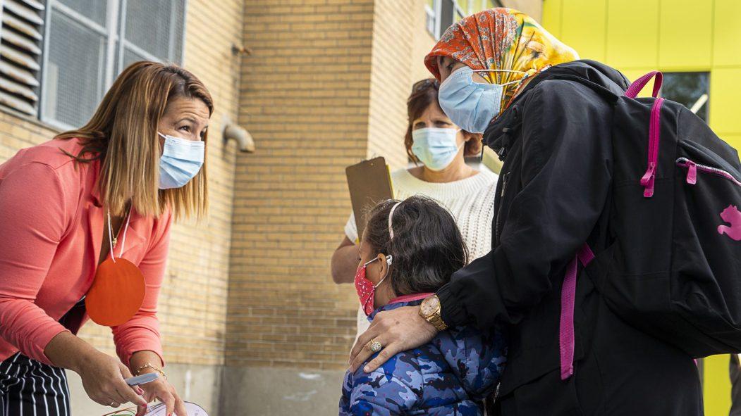 Une enfant masquée est accueillie avec sa mère à l'école primaire Philippe-Labarre, lors de la première rentrée scolaire depuis le début de la pandémie de COVID-19.