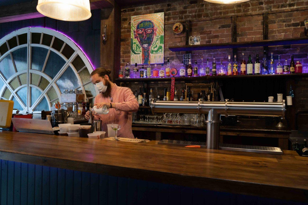 Le mixologue Justin Petitclerc préparant un cocktail derrière son bar