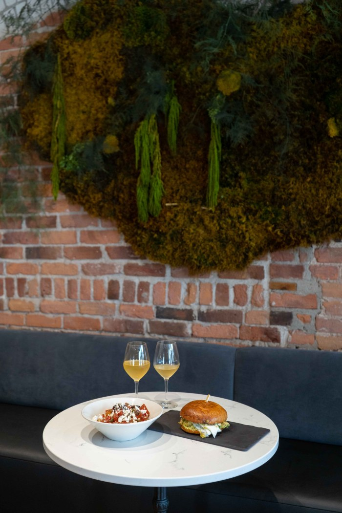 Deux plats et deux coupes de vin déposés sur une table dans un restaurant face à un mur de briques recouvert de verdure
