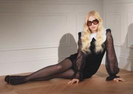 Mannequin assise sur le sol revêtant une robe noire et des lunettes de soleil
