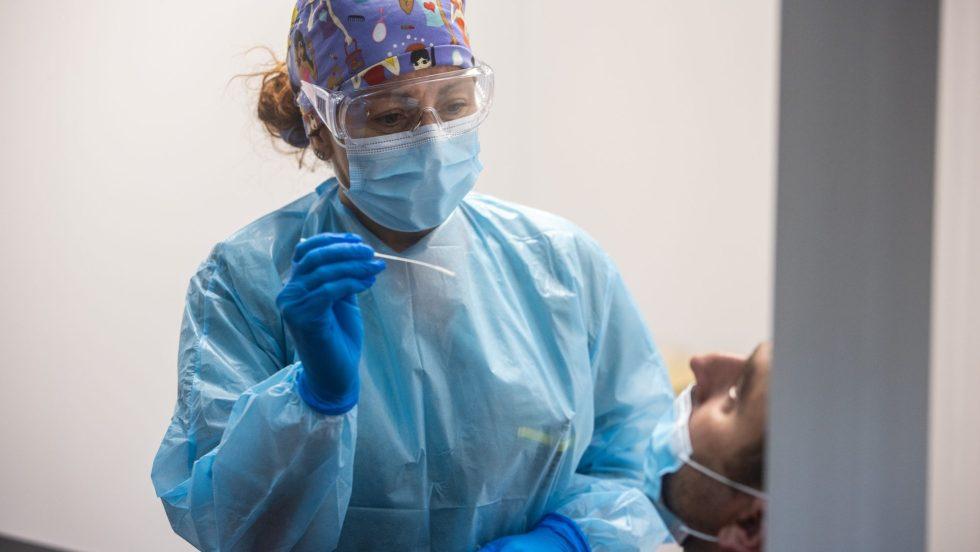 Une infirmière masquée procède à un test de dépistage du coronavirus.