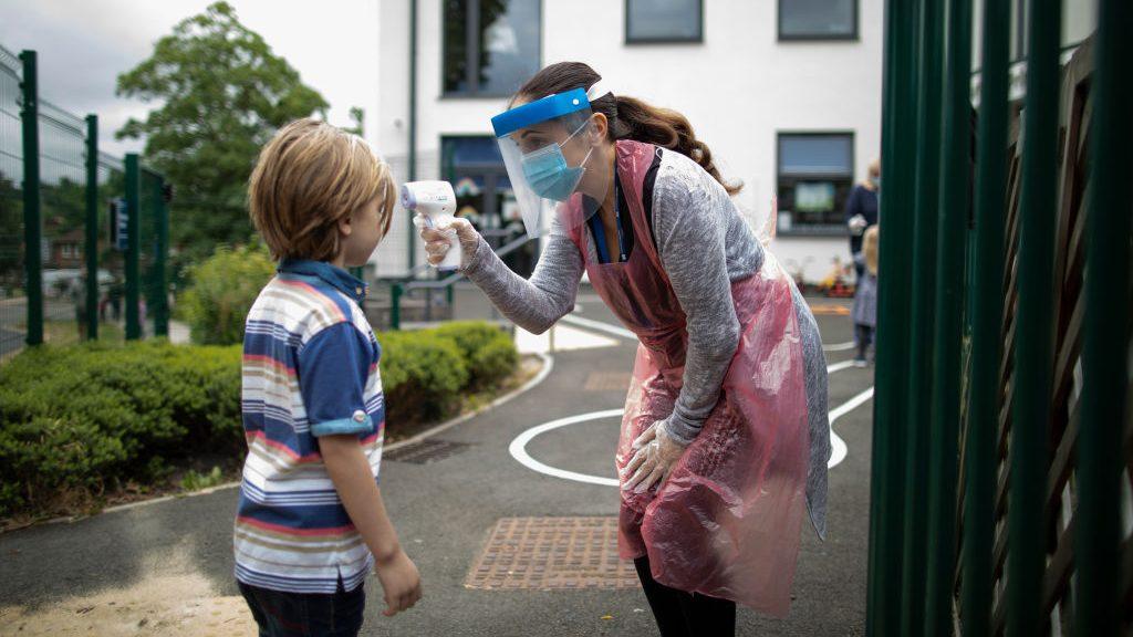 Un enfant se fait prendre la température par une dame portant une visière contre la COVID-19