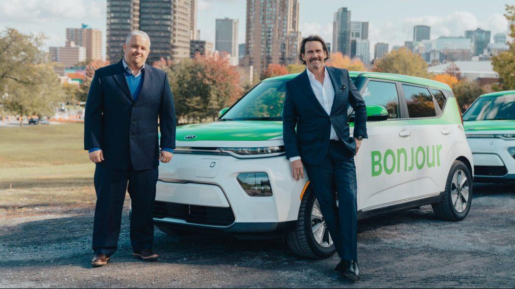 Pierre Karl Péladeau et le directeur de Téo Taxi devant un de leur véhicule électrique