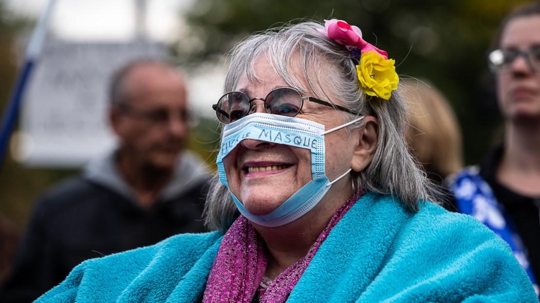 Une femme manifeste contre le port du masque à Montréal.