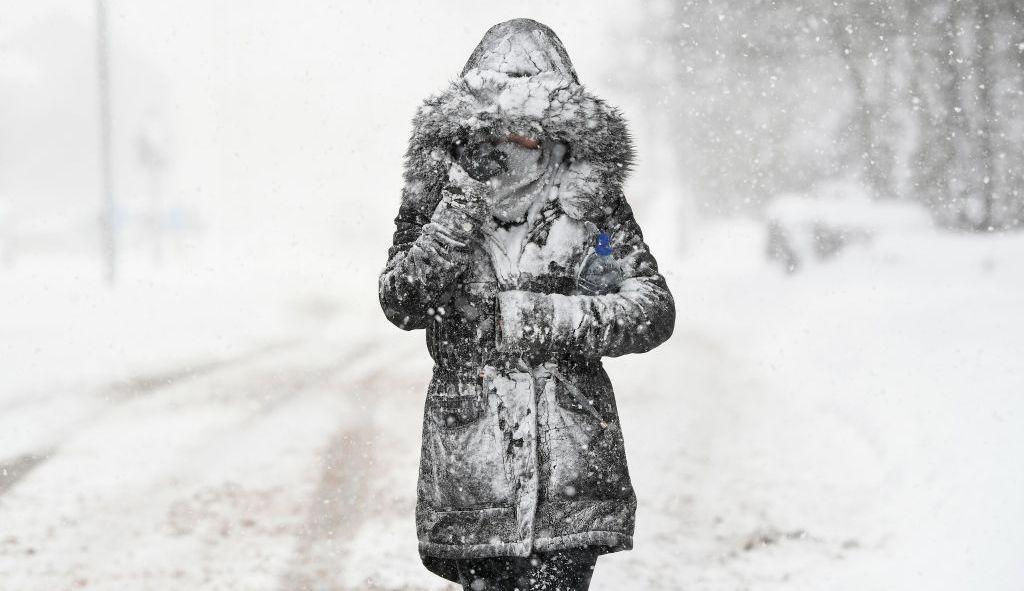 Une jeune femme marche au coeur de l'hiver
