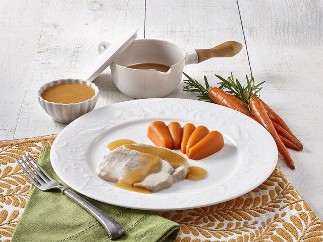 Une assiette de poulet et de carottes détexturés.