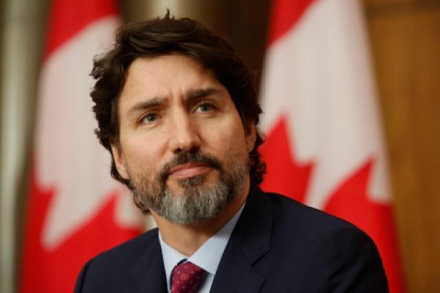 Le premier ministre Justin Trudeau devant des drapeaux du Canada lors d'un point de presse sur la COVID-19.