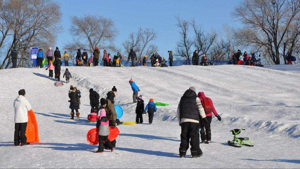 Des familles à la butte à glisser du parc Arthur-Therrien.