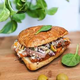 Sandwich italien : Tranches de seitan grillées, mozzarella végan, olives vertes, poivrons, oignons rouges, vegenaise et sauce red hot dans un pain ciabatta grillé