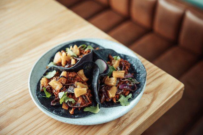 Une assiette contenant trois tacos végétalien posée sur une table
