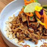 Pad thaï : Nouilles de riz avec chou frisé, carottes, oignons, tofu grillé et sauce aux arachides. Servi avec fèves germées, lime et coriandre.