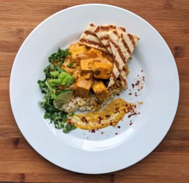 Tofu au beurre : Tofu avec sauce crémeuse aux épices indiennes, pois verts et riz basmati. Servi avec pain naan et coriandre.