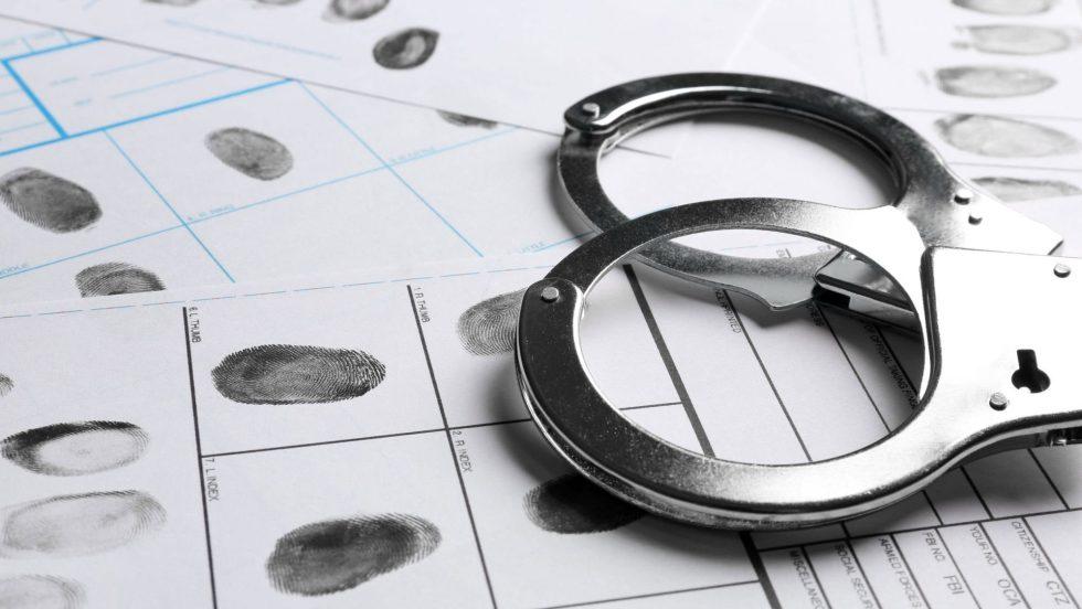 des menottes et des empreintes digitales symbolisant une personne avec un casier judiciaire.