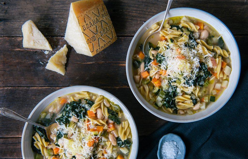 Deux bols de soupe minestrone déposés sur une table en bois. Un morceau de fromage et du sel sont aussi sur la table.