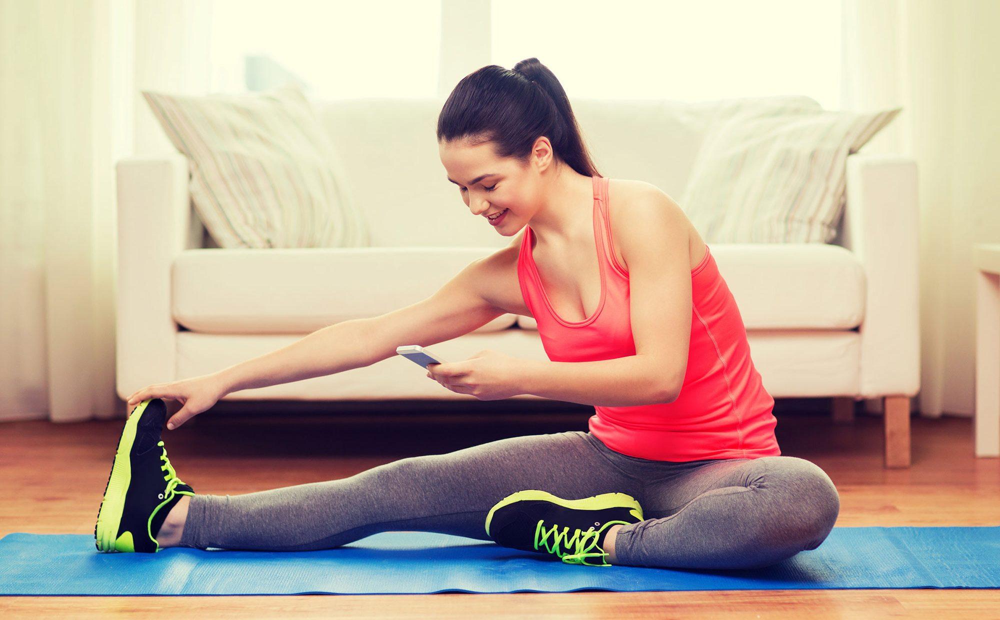 Fitness à la maison: jeune femme streching sur le plancher smartphone à la main devant son divan.