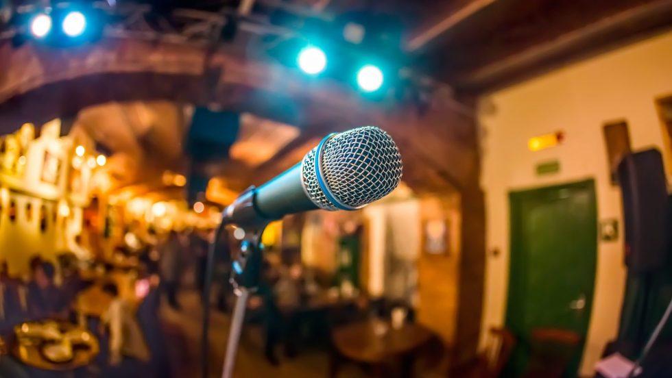 Un microphone placé sur une scène pour un spectacle d'humour