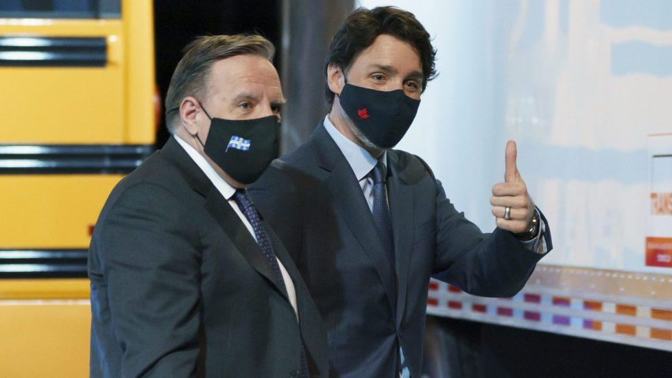 François Legault et Justin Trudeau devant un autobus jaune