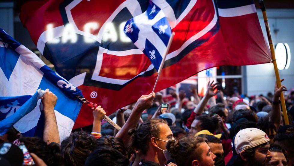 Un drapeau des Canadiens de Montréal flotte au-dessus d'une foule de partisans réunis devant le restaurant La Cage près du Centre Bell.