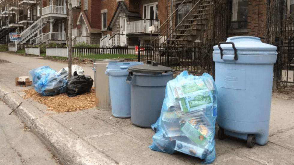 Des sacs et bacs de déchets et de matières résiduelles le long d'un trottoir.