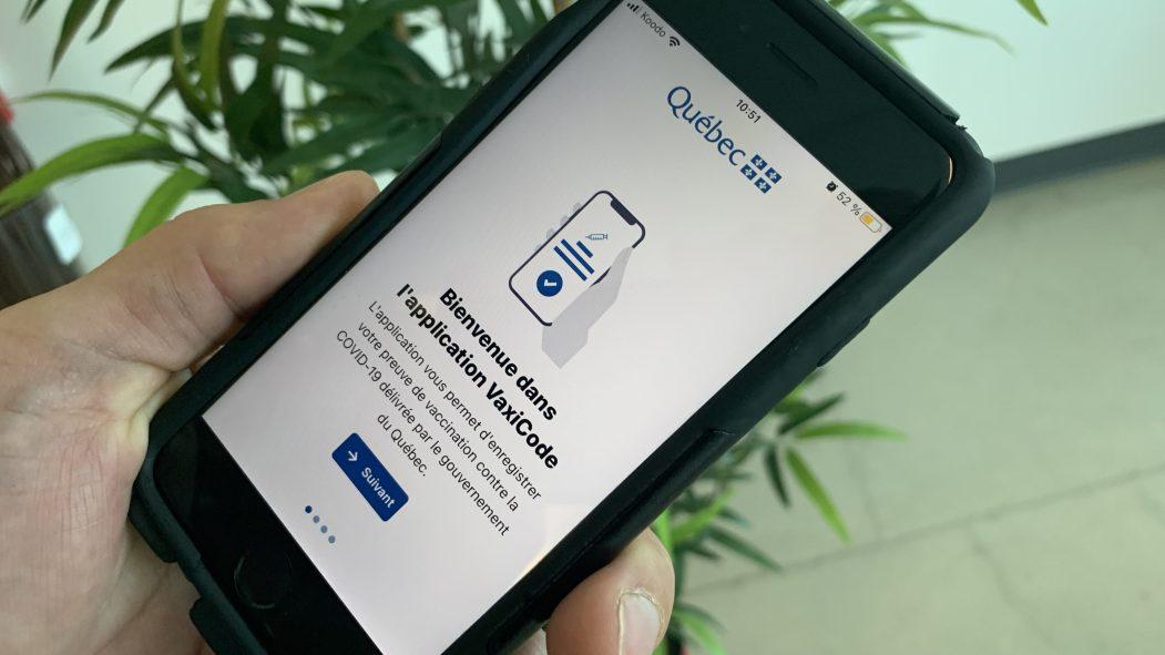 Une main tient un téléphone intelligent. L'application VaxiCode, la plus téléchargée de l'AppStore, est affichée