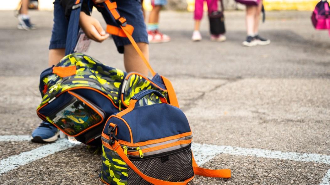 Un enfant soulève son sac à dos lors de la rentrée scolaire dans une école de Montréal, pendant la pandémie de COVID-19.