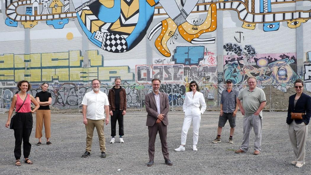 Les représentants de l'arrondissement du Plateau-Mont-Royal, dont le maire Luc Rabouin (au centre), et des membres de la communauté artistique se tiennent devant une murale située sur la rue de Gaspé