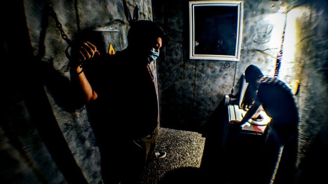 Un homme est enchaîné dans une pièce de jeu d'évasion.À sa droite un homme cherche dans une toilette. La pièce est sombre.