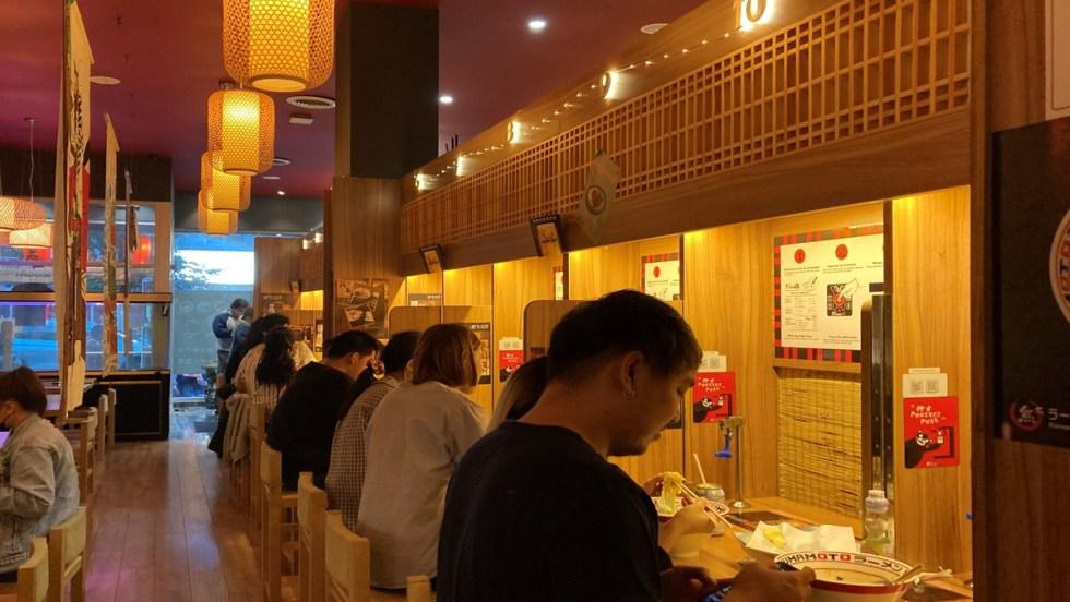 Des clients assis à un comptoir du restaurant japonais Kumamoto Ramen.
